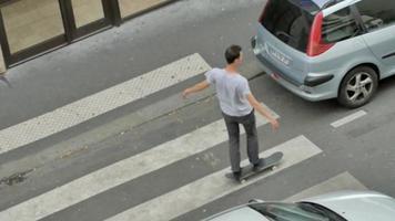 un joven hace un truco de skate mientras monta su patineta en la calle en parís, francia. video