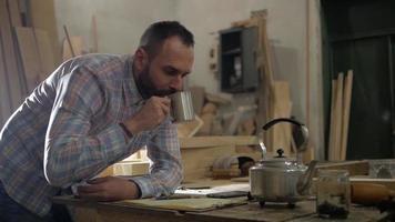 Man in A Carpentry Workshop Drinking Tea video