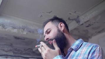 chico barbudo fuma un cigarrillo y bebe café video