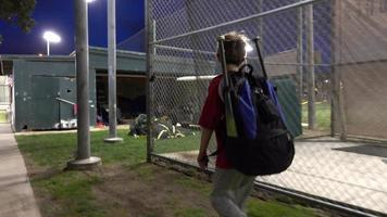 A boy walking with his bat bag after a little league baseball game. video