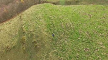 Vista aérea de un corredor de pista corriendo sobre la hierba. video