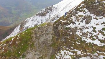 Vista aérea de un corredor de pista corriendo por la cresta de una montaña nevada. video