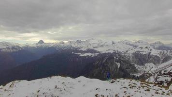 Vista aérea de un corredor de pista corriendo hacia la cima de una montaña nevada. video