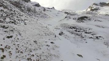 un corredor de senderos sube por una montaña nevada. video