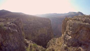 Aerial view of a woman balancing while tightrope walking and slacklining across a canyon. video