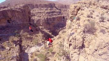 Aerial view of a man balancing while tightrope walking and slacklining across a canyon. video