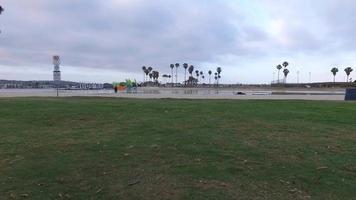 tiro de seguimiento de un hombre trotando sobre el césped cerca de una bahía. video