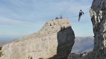 A man tries to balance while slacklining on a tightrope in the mountains. video