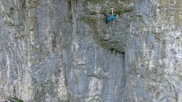 Aerial view of a man rock climbing up a mountain. video