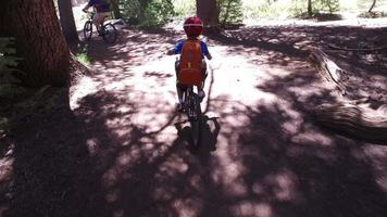 A boy rides his mountain bike on a singletrack dirt trail in the woods. video