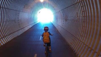 A boy rides his mountain bike through a tunnel on a paved trail in the woods. video