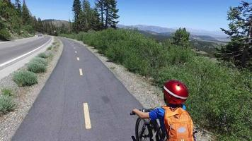 A boy rides his mountain bike on a paved trail in the woods. video