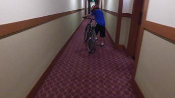 A boy rides his mountain bike in a hotel hallway. video