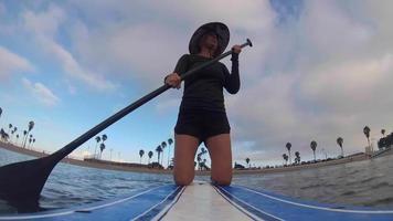 pov de una mujer remando de rodillas en una tabla de remo de pie. video