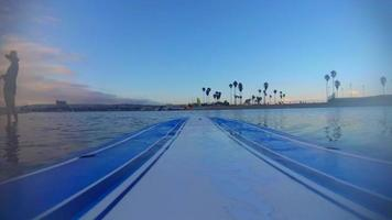 pov de una tabla de surf de remo en un lago al atardecer. video