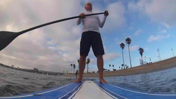 pov de un hombre remando una tabla de remo de pie en un lago. video