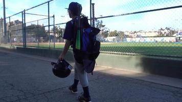 A boy walks to a little league baseball game. video