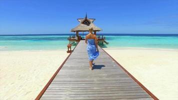 uma mulher caminhando em um cais do cais ao longo de uma praia de ilha tropical. video
