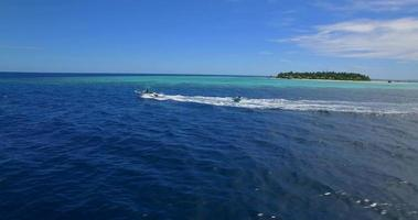 Vista aérea de un hombre y una mujer en un tubo inflable remolcando detrás de un bote a una isla tropical. video
