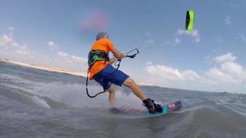 un hombre kiteboard surfeando sobre las olas en la playa. video