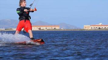 un hombre haciendo kitesurf y haciendo un truco de salto en una tabla de kite. video