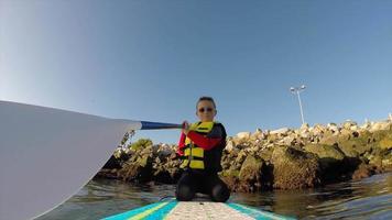 punto de vista de un niño remando en una tabla de remo de pie en un puerto deportivo. video