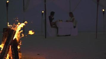 A man and woman have dinner on a tropical island beach with a campfire. video