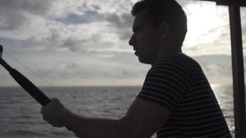 silhueta de um homem pescando de um barco. video