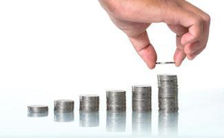 El concepto de ahorrar dinero, mano poniendo dinero pila de monedas creciendo sobre fondo blanco. foto