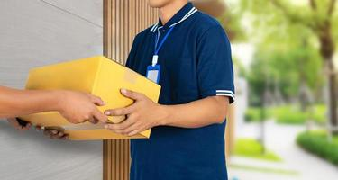 Man hand accepting a delivery service boxes package from delivery man photo