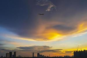 Silhouette of Bangkok at sunset with airplane flying in twilight sky photo