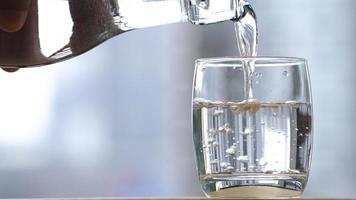 Beber agua vertida en un vaso sobre la mesa. foto