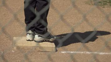 A boy is on base while playing in a little league baseball game. video