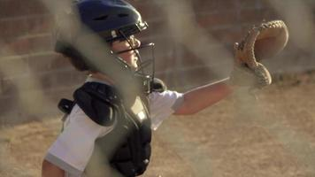 A boy gets hit in the face mask by the ball while playing catcher in a little league baseball game. video