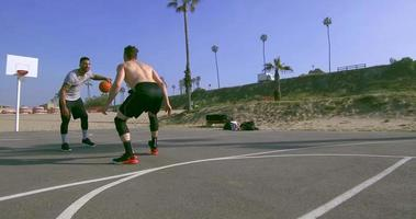 A man dribbles while playing one-on-one basketball hoops on a beach court. video