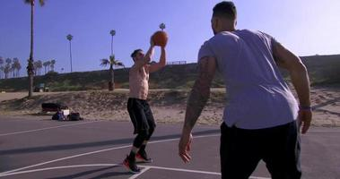 A man takes a jump shot while playing one-on-one basketball hoops on a beach court. video