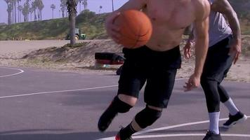 A man does a slam dunk while playing one-on-one basketball hoops on a beach court. video