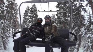 Standpunkt von Snowboardern, die auf einem Lift in einem Skigebiet fahren. video