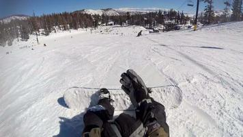 pov eines Snowboarders, der sich auf seinem Snowboard in seine Bindungen anschnallt. video