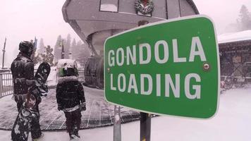 Gondelladeschild und Snowboarder an einem Lift in einem Skigebiet. video