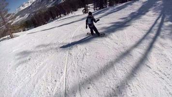eine Frau Snowboarder Snowboarden bergab in einem Skigebiet. video