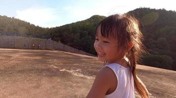 Happy little girl playing in summer park. Happy childhood. Girl run along road at sunset. video