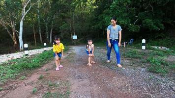 famille heureuse qui court dans le parc d'été. la mère et les enfants courent le long de la route au coucher du soleil. la famille a passé ensemble en vacances. video