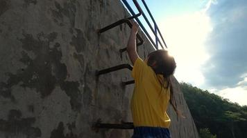 Little girl climbing the metal stairs on playground. happy childhood concept. video