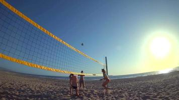 POV of women players playing beach volleyball with a girl diving to dig a ball. video