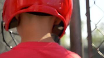 un niño practica béisbol de ligas menores en las jaulas de bateo y entra a la jaula. video
