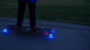 een jongen rijdt op een skateboard met led-verlichtingswielen in een buurt. video