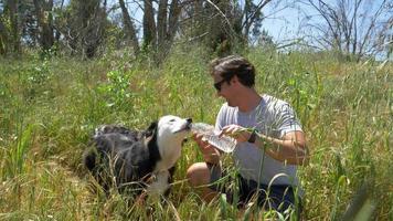 un hombre ayuda a su perro a beber agua después de correr por un sendero. video