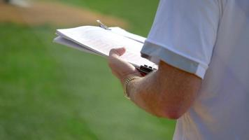 A coach with his clipboard notebook in a little league baseball game. video