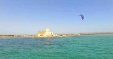 un hombre haciendo kitesurf en una tabla de kitesurf en hidroala. video